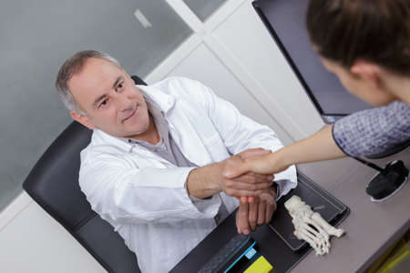 A doctor shaking hand with a patient in his office in a hospital Stock Photo