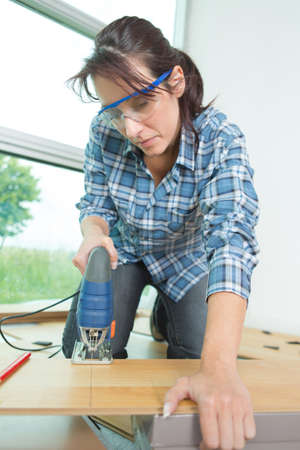 female worker cutting wood with angle grinder