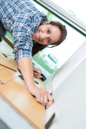 A close-up of a craftswoman measuring a wooden plank Stock Photo