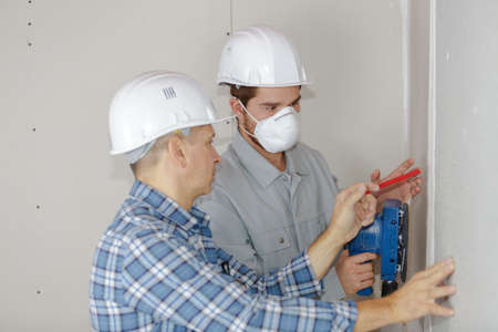 home improvement workers in protective mask working with sander