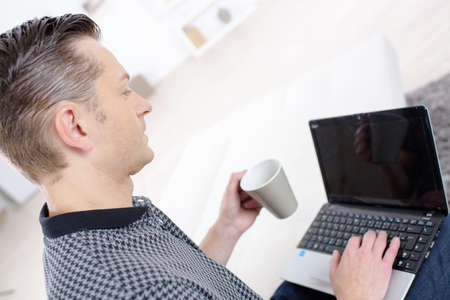 man with laptop drinking coffee or tea Stock Photo