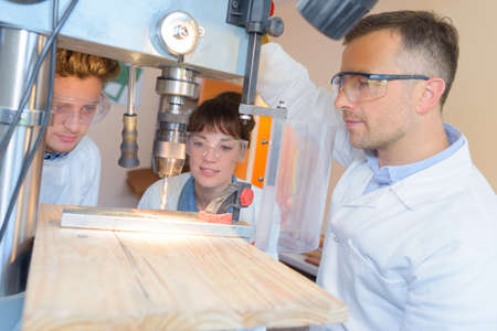 engineer training female and male apprentice on milling machine