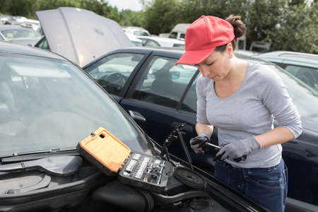A female worker checking the cars LPG engine