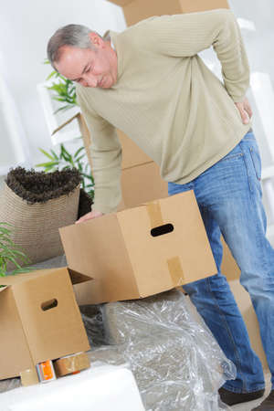 back ache: man is moving having pain in his back while packing