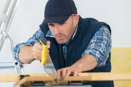 carpenter sawing wood with hand saw Stock Photo