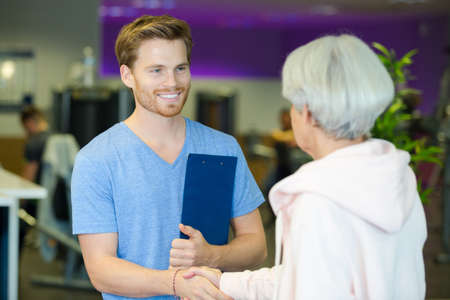 A smiling young physical trainer shaking hands with a fit senior man Stock Photo