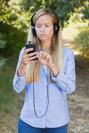 beautiful young woman rinsert her earphones during walk