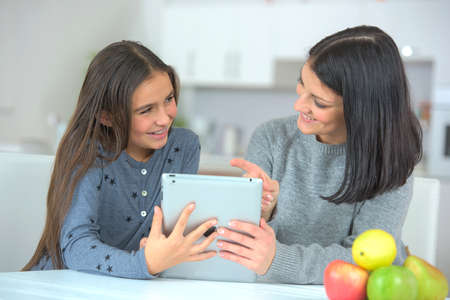 mother showing media content to daughter