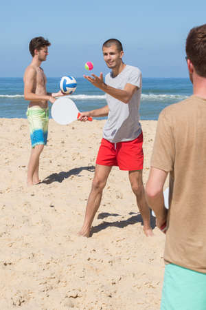 Three friends relaxing on a sandy and playing racket ball