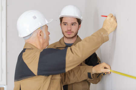 builders drawing the line on the wall Stock Photo