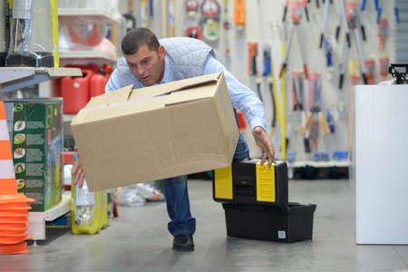 worker with backache while lifting box in the warehouse Stock Photo