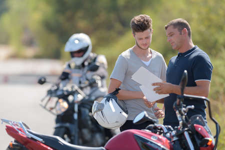 young driver and instructor checking driving school track