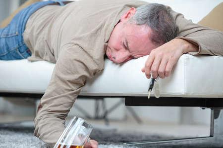 senior man sleep with glass of beer on the sofa