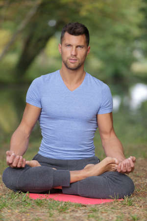 reiki: man practising yoga in the forest