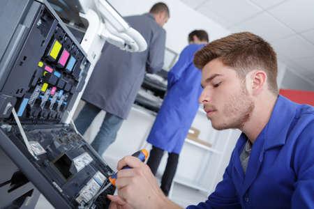 apprentice fixing a printer