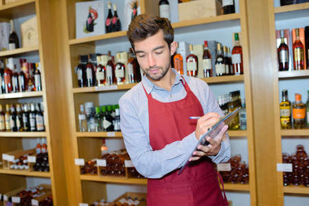 salesman taking inventory in wine store Stock Photo