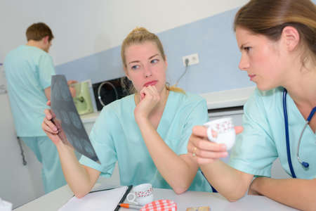 nurses looking at the radio result during break Stock Photo
