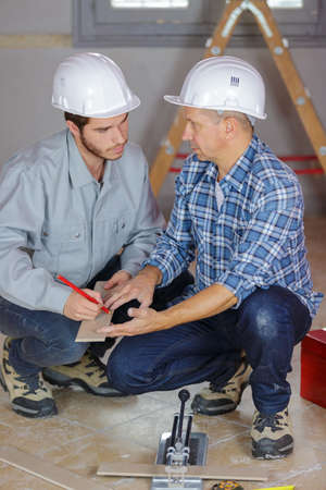 builders laying tiles Stock Photo