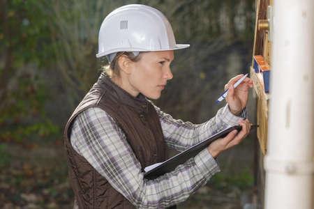 jonge vrouwelijke werknemer die meter leest