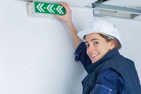 light duty: female electrician installing emergency light