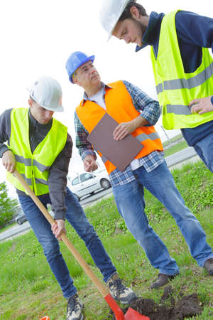 young men digging a hole on the ground Stock Photo