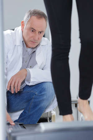 doctor observing woman on treadmill Stock Photo
