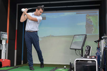 Man practicing golf swing using simulator Stockfoto