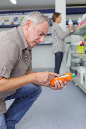 Senior man reading the label on a product