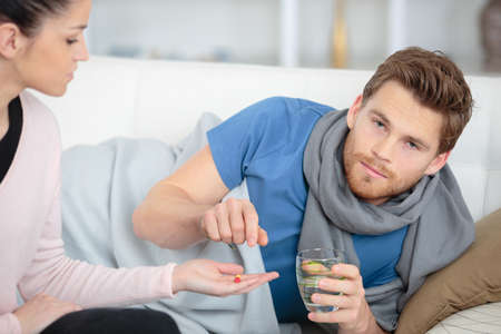 Poorly man accepting tablet from girlfriend