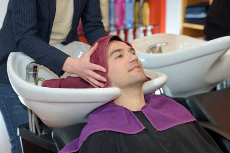toweling: Hairdresser using towel to dry mans hair Stock Photo