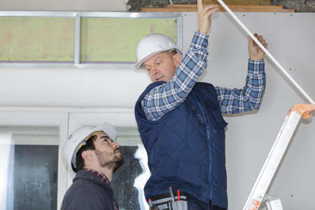 Contractor on stepladder talking to colleague on the ground Stock Photo