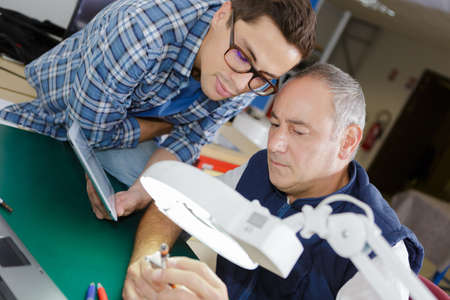light duty: product engineers observing the defective mechanism Stock Photo