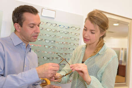 Optician advising customer on choice of spectacles