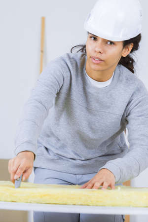 Portrait of female contractor cutting insulation