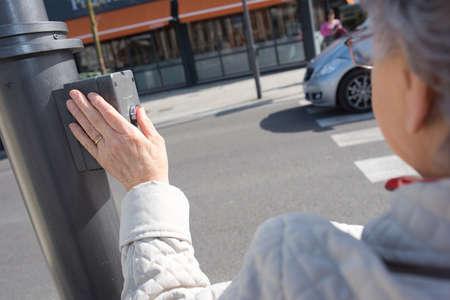 Ouderen voetgangers drukknop om de weg over te steken