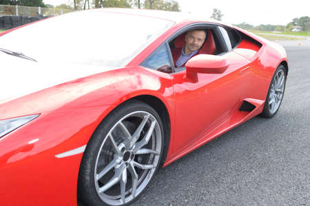 Portrait of man in red sports car