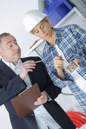 Man in suit criticising woman wiring plug socket