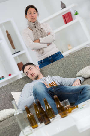 Woman looking disdainfully at young man surrounded by empty beer bottles