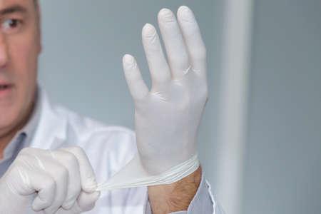 Man putting on a latex glove
