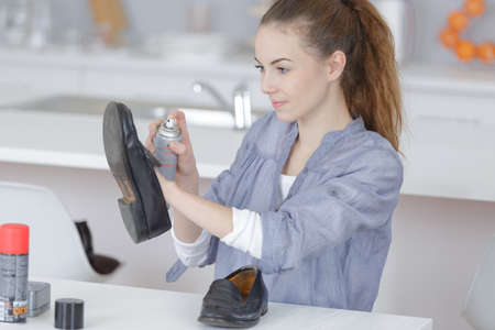 Young lady spraying shoe Stock Photo