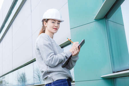 Portrait of lady with clipboard outside a building