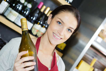 Shop assistant holding bottle of white wine