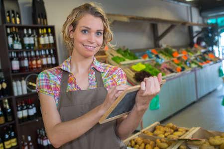 Shopkeeper writing on slate Stock Photo