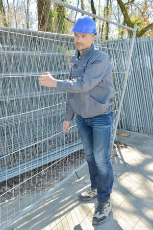 Man carrying metal fence Stock Photo