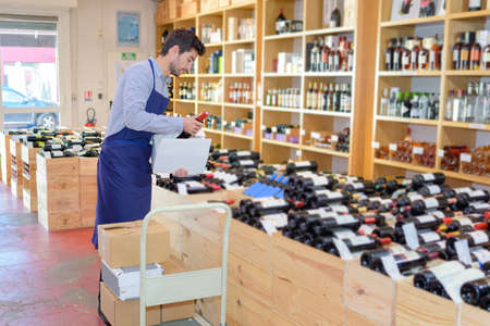 Wine merchant unpacking bottles