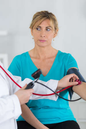 Middle aged woman having blood pressure checked Imagens