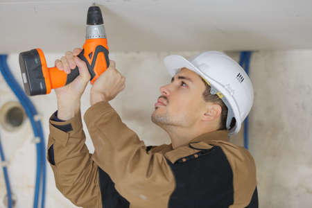 Man drilling hole into ceiling