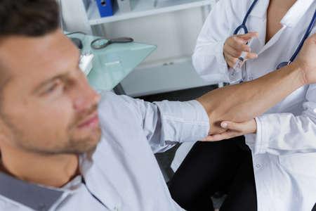 hombre que tiene la inyección en el brazo