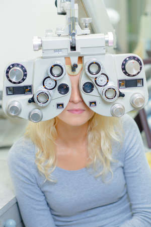 Woman behind opticians eye testing equipment