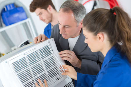 Team working on air conditioning unit Stock Photo